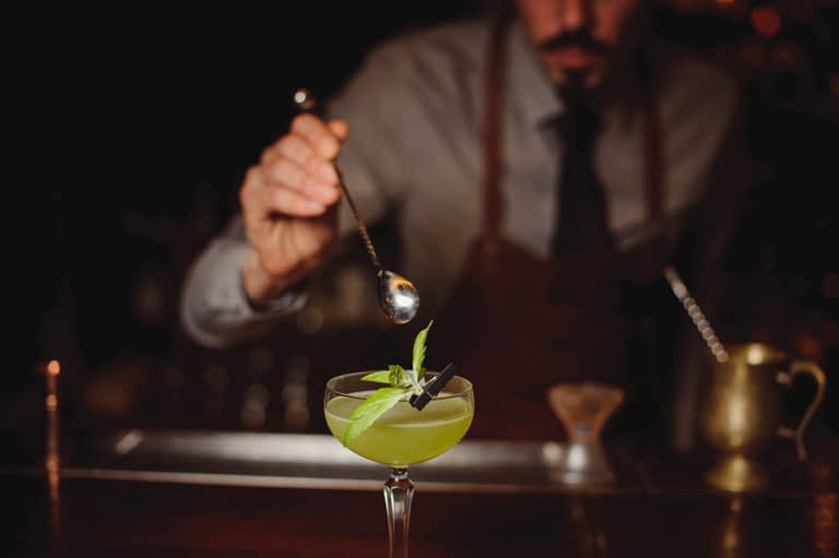 NYC cocktail consultant garnishes a cocktail.
