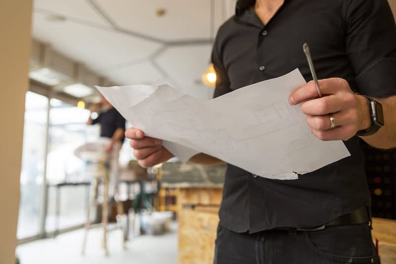 A man holds some blueprints while others do construction work in a restaurant.