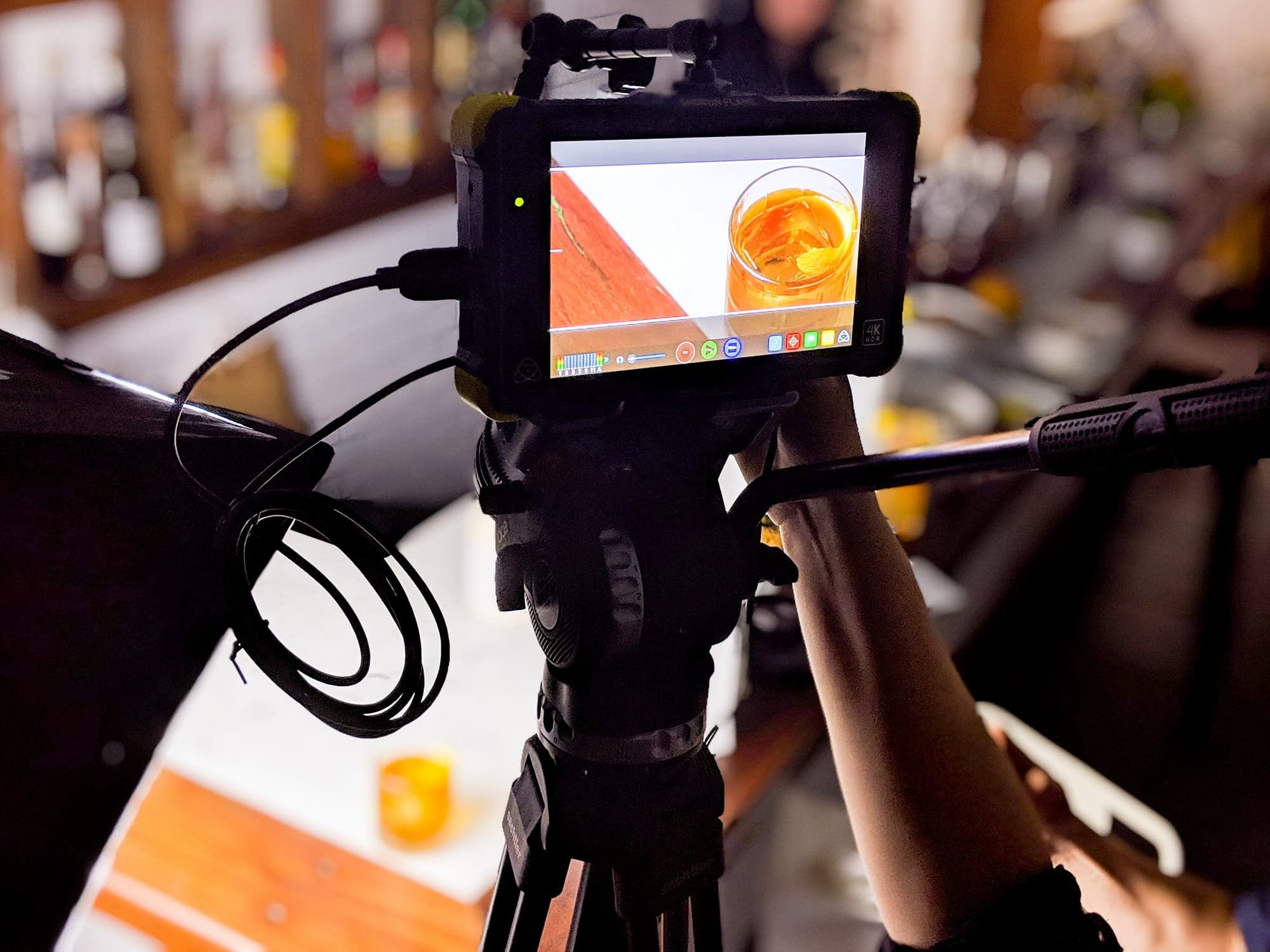 Large camera viewer displaying a product shot for a cocktail in a bar. Cocktail is out-of-focus but visible in the background.