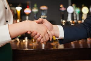 Close up on colleagues shaking hands during meeting in a classy bar