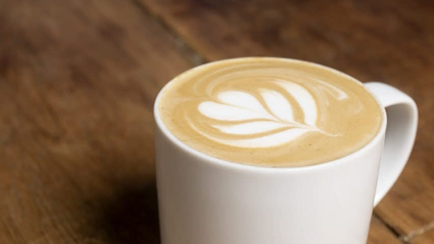 A latte decorated with a tulip is served in a white ceramic mug sitting a wooden surface.