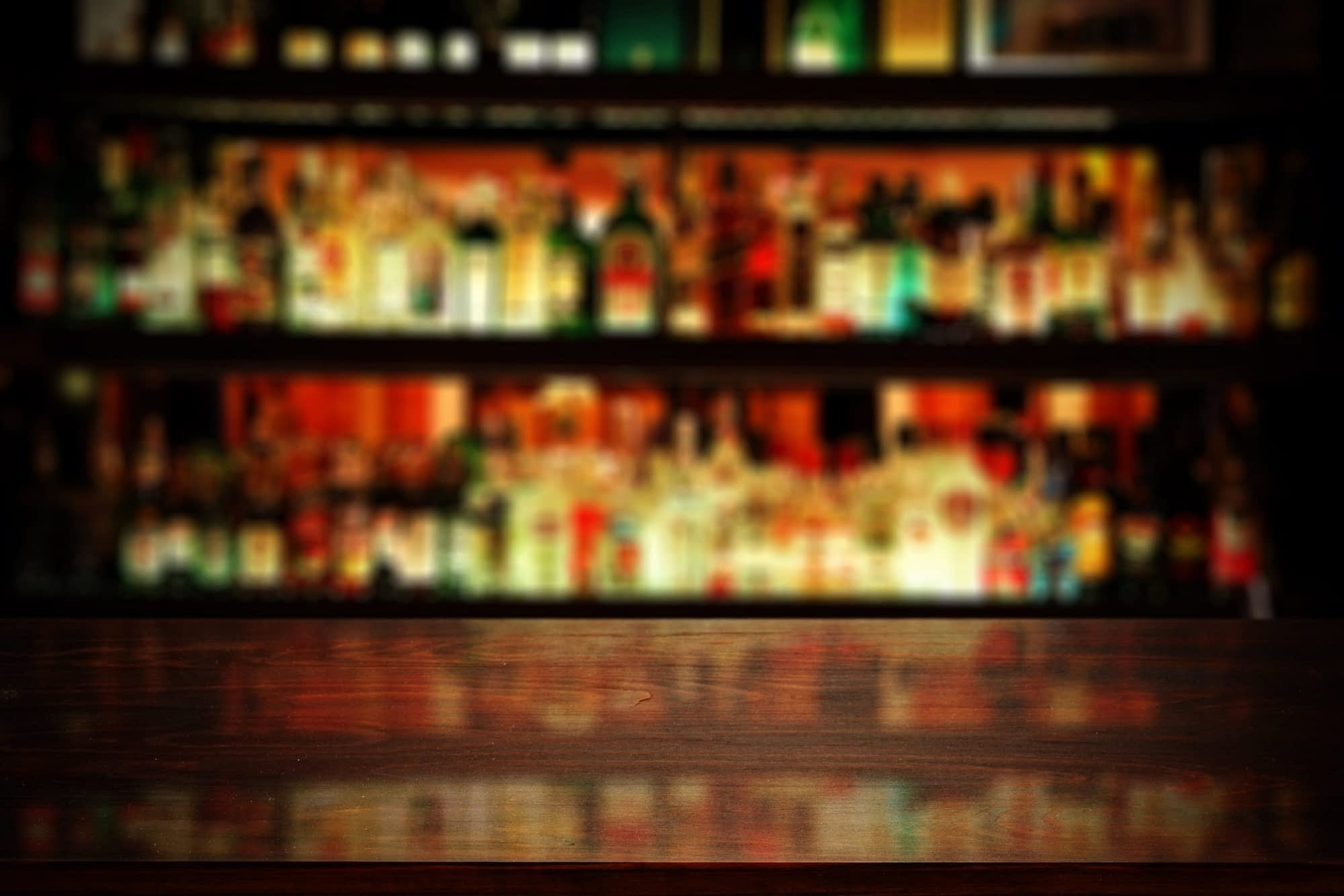 An out-of-focus back bar is reflected in a wooden bar top.
