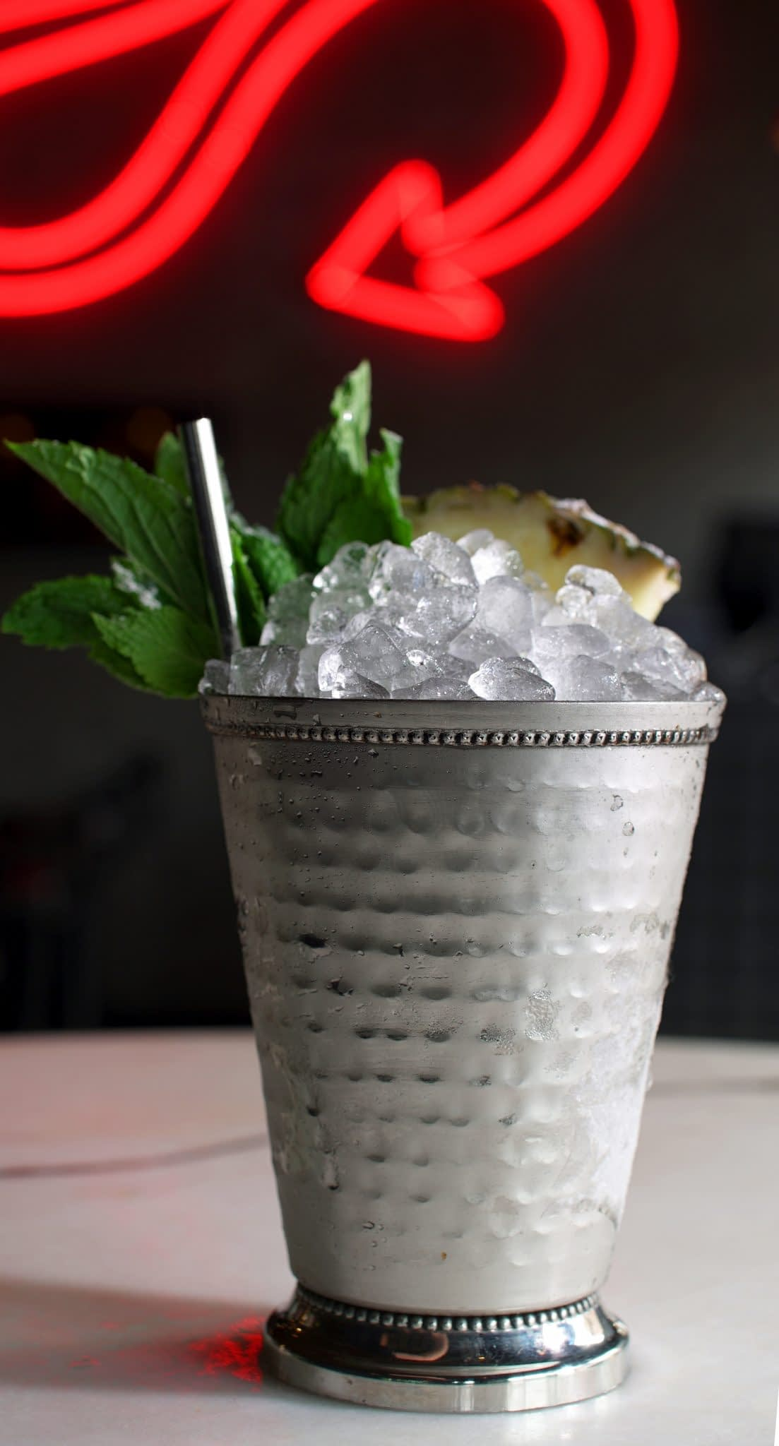 A julep-style cocktail served in a silver julep cup is filled with pebble ice and garnished with a mint sprig, pineapple wedge, and metal straw and then dusted with powdered sugar. The cocktail sits on a marble table with a neon devil's tail out of focus in the background.