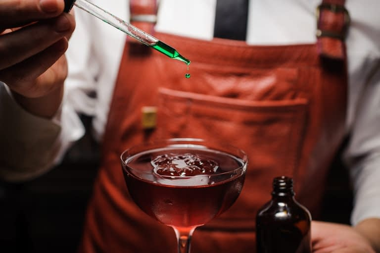 Beverage consultant adds bitters to a stirred cocktail.