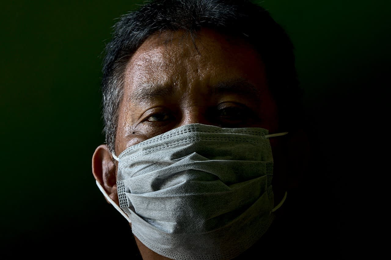 An exhuasted Latinx man wearing a surgical mask looks directly at camera.