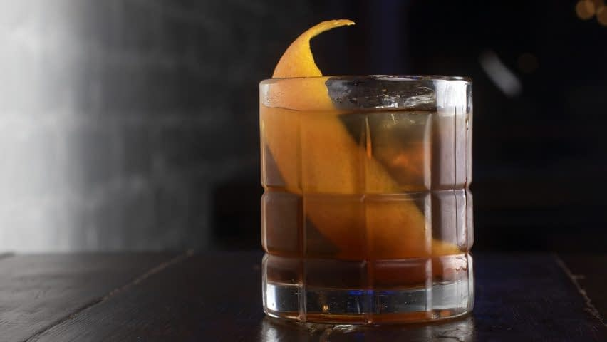 Dark brown old-fashioned style cocktail is served with a large citrus peel.