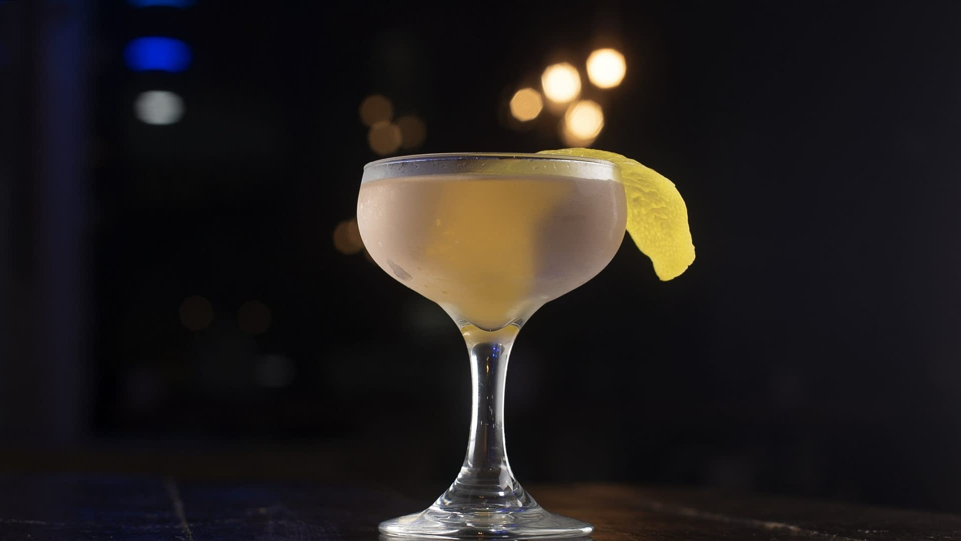 A blush colored cocktail served in a coupe and garnished with a lemon twist sits on top of a wooden surface on a dark background.