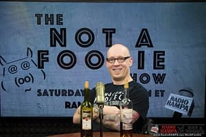 Vincent Vee sits behind some bottles of wine and a studio microphone with the logo of the Notafoodie show in the background.