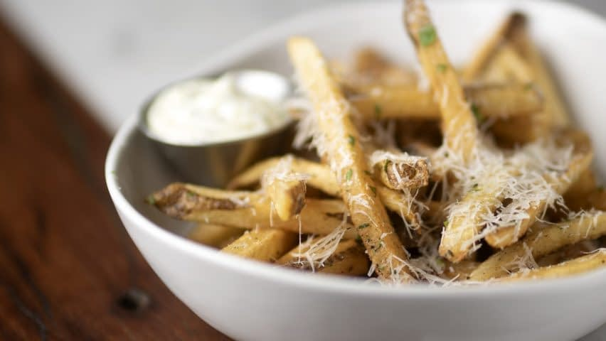 Golden brown french fries with light flakes of gran padano cheese and parsley sit in a bowl with a metal ramekin.