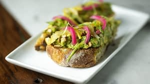 Fresh bread topped with avocado, poached lemons, sunflower seeds, and pickled onions sits on a white plate on top of a stone and wooden surface.