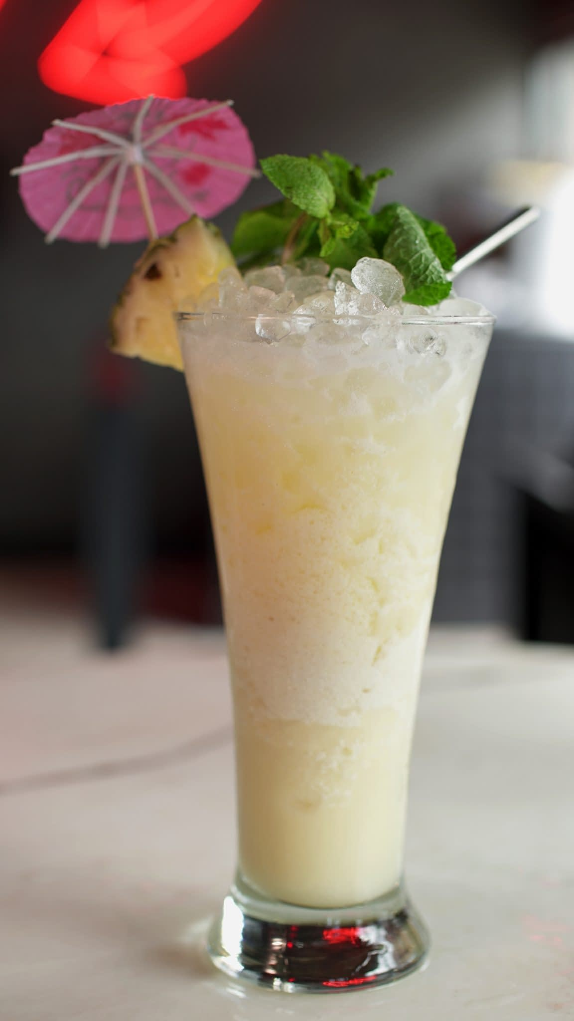 A cream colored cocktail served with pebble ice in a tall pilsner glass is garnished with a mint sprig, pineapple wedge, and cocktail parasol. The drink sits on an out of focus marble table with a neon sign faintly visible in the background.