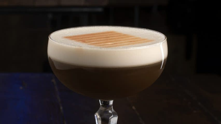A dark brown colored eggwhite cocktail with a light brown foam sits in a crystal coupe. The foam has a logo sprayed-stenciled on top.
