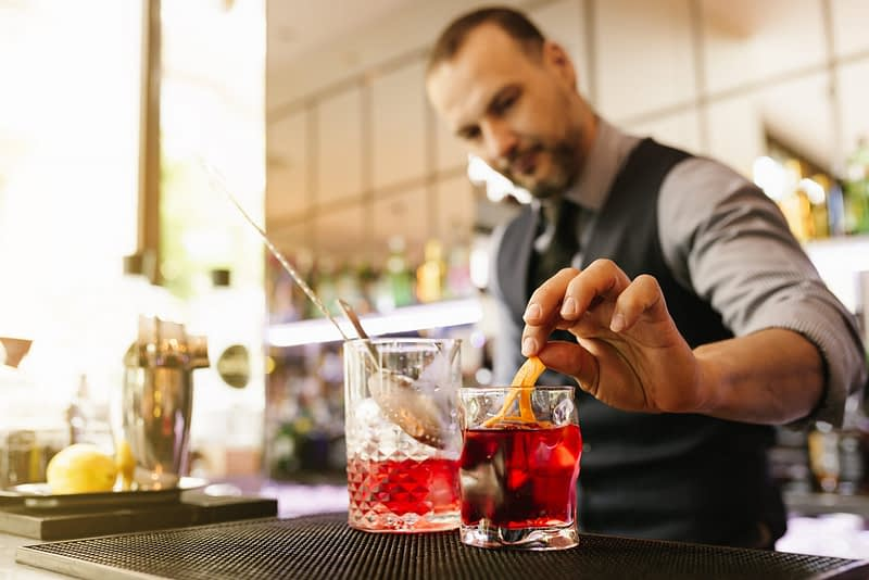 A cocktail consultant garnishes a cocktail.