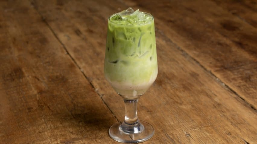 An iced matcha latte fades from green to white in a beer tulip and sits on a wooden surface.