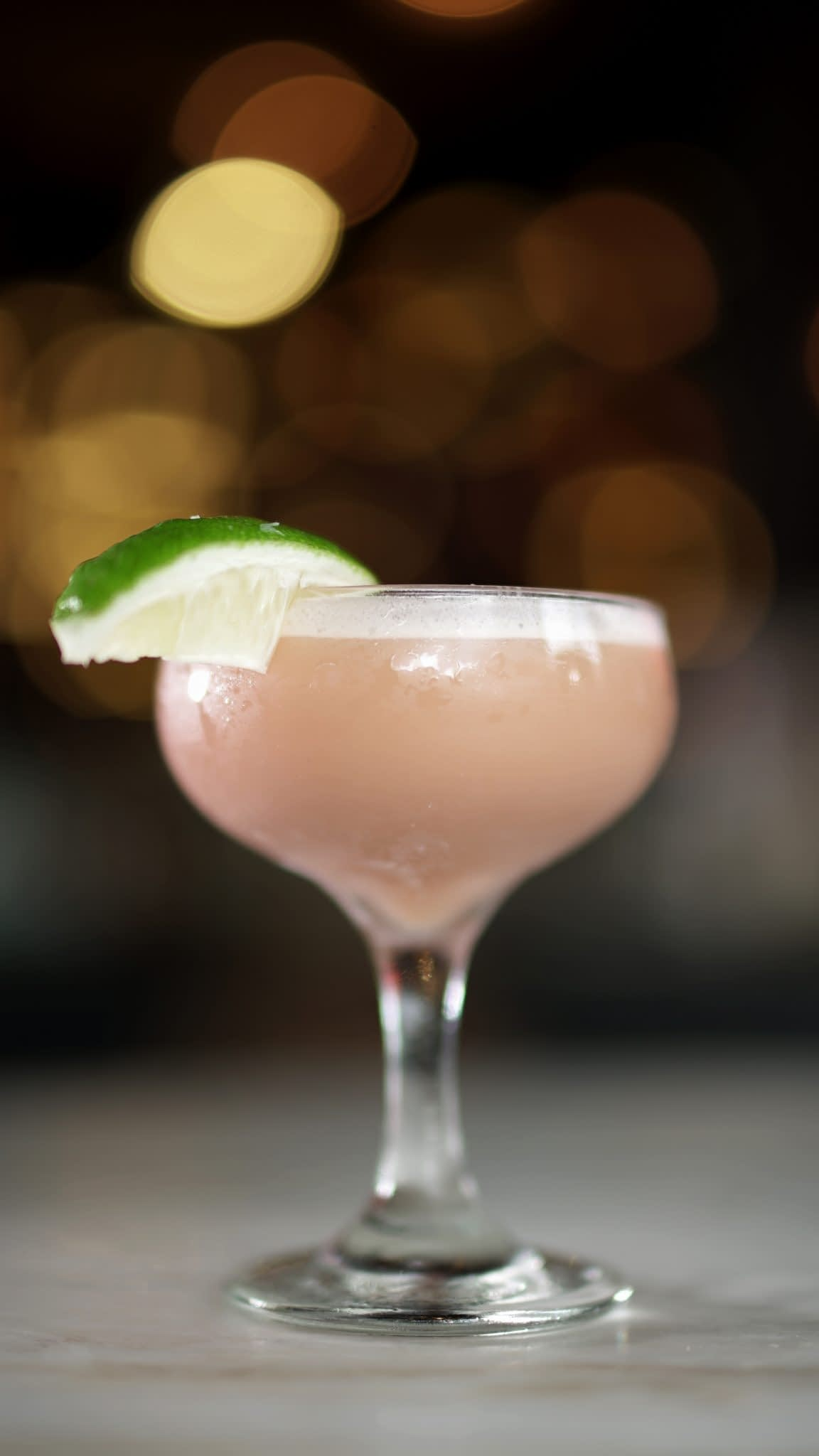 A creamy pink cocktail with bright white foam is served in a coupe glass with a lime wedge garnish. The cocktail sits on a marble table with a dark background.