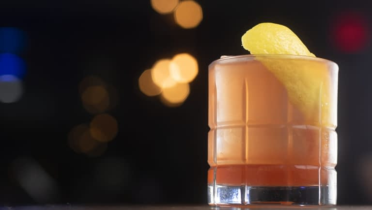 A brightly colored cocktail in a contoured rocks glass is garnished with a large lemon twist.