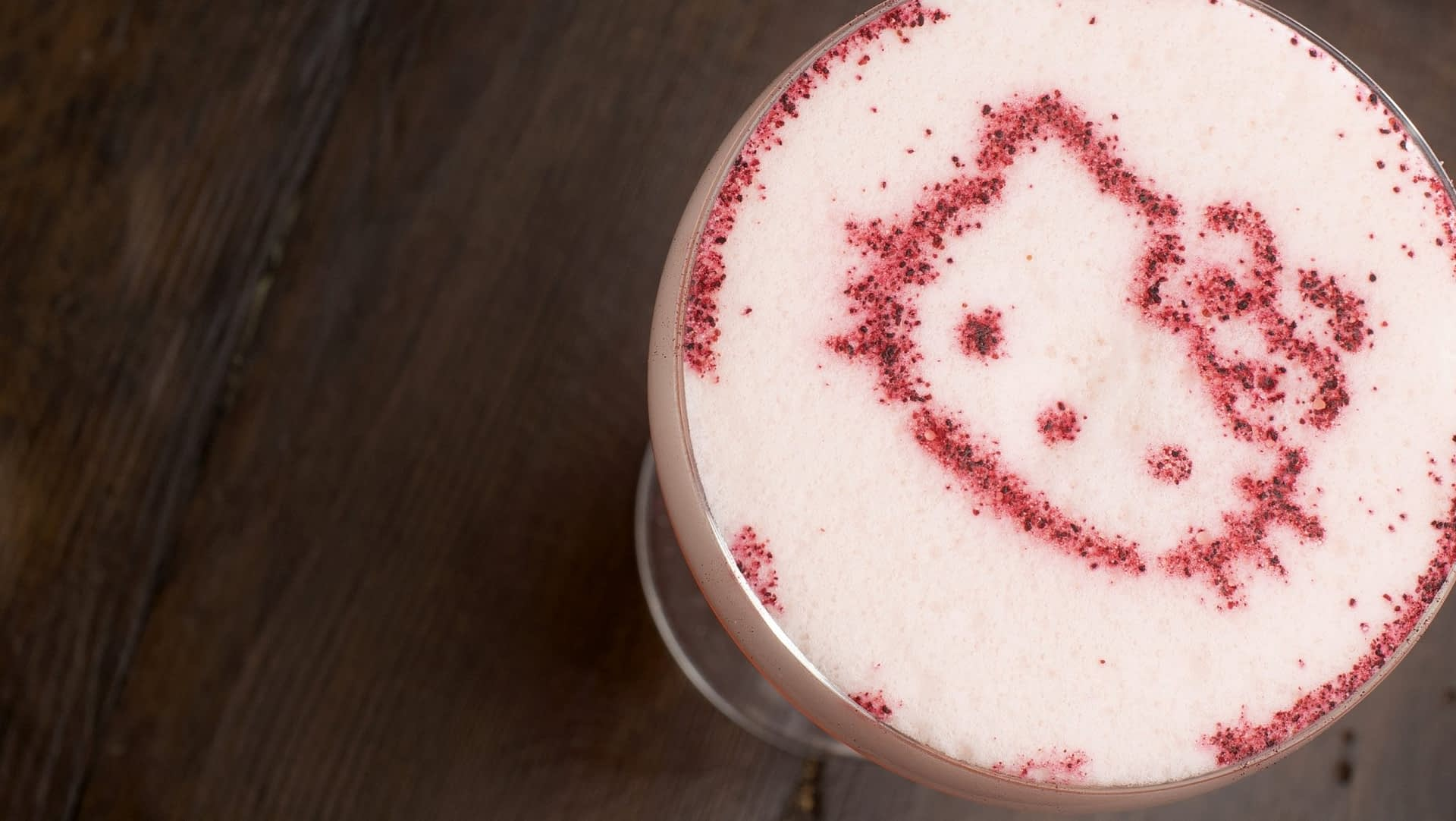 Overhead view of a pink eggwhite cocktail garnished with powdered berries in the shape of hello kitty is served on a wooden surface.