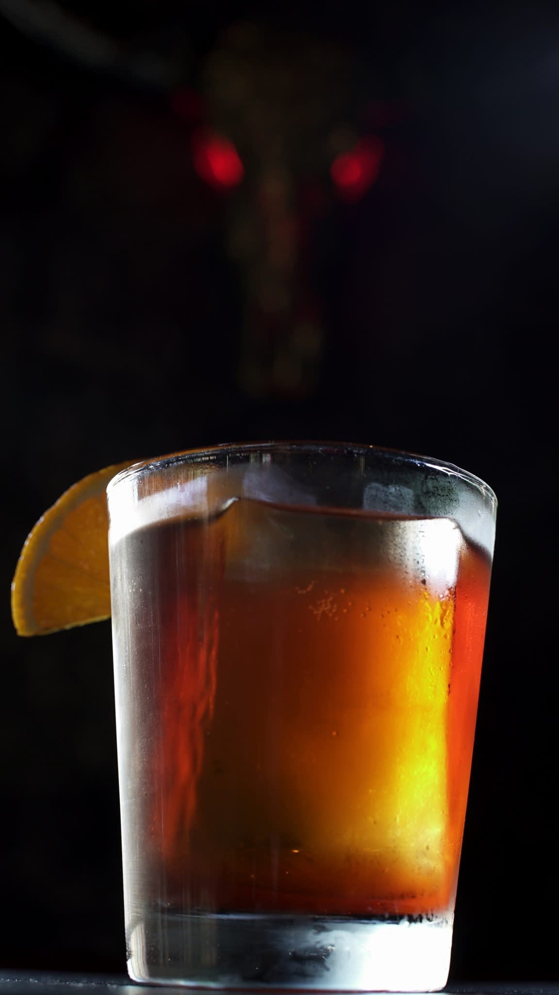 A reddish brown cocktail served in a double rocks glass on crystal clear ice is garnished with an orange wedge. The drink hovers over a black background. An ominous skull with glowing red eyes is faintly visible in the background.